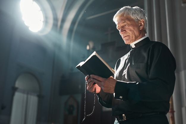 教会に立って式典中に聖書を読んでいる大祭司
