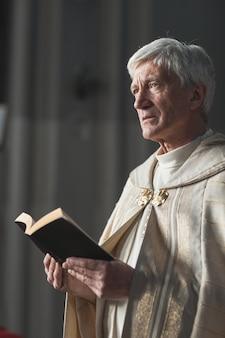 教会での結婚式中に聖書を持って立って祈りを読んでいる先輩司祭