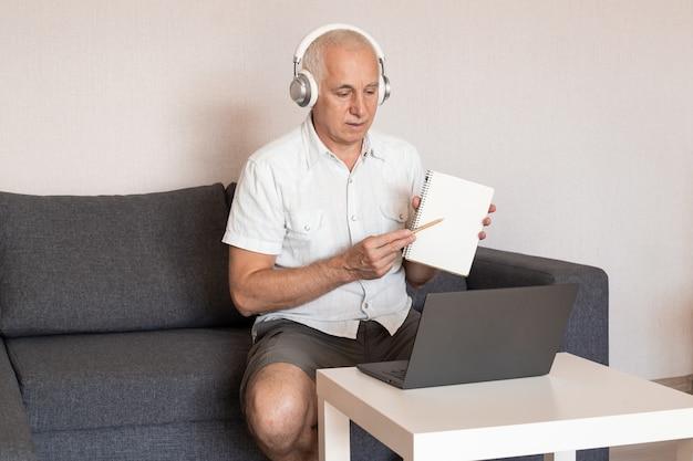 Старший профессор проводит онлайн-лекцию, сидя дома