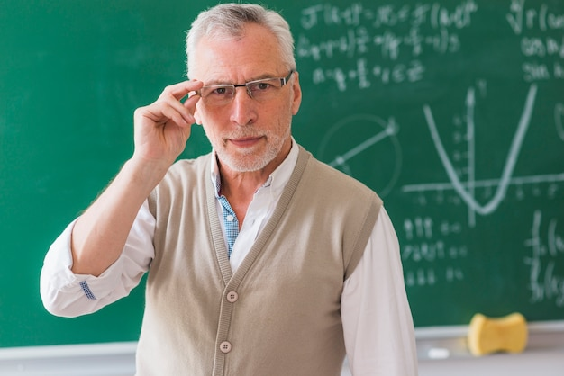 Senior professor correcting glasses against chalkboard with math problem