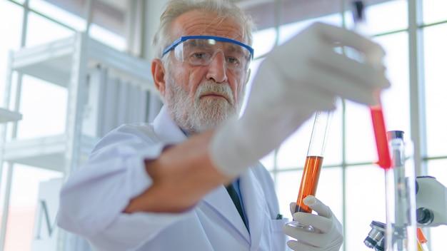 上級教授の男性研究者は、実験室試験の科学について、顔の濃度で薬液チューブをテストします。インテリアの白い実験室と机の上の設備。