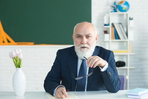 上級教授の真面目な学校の先生または大学が学校に戻って講義する