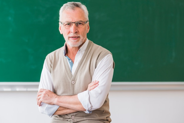 Senior professor with arms crossed looking at camera against empty chalkboard