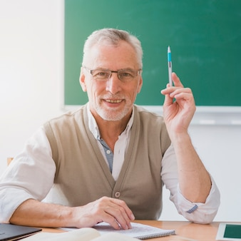 Senior professor with raised hand holding pen in classroom