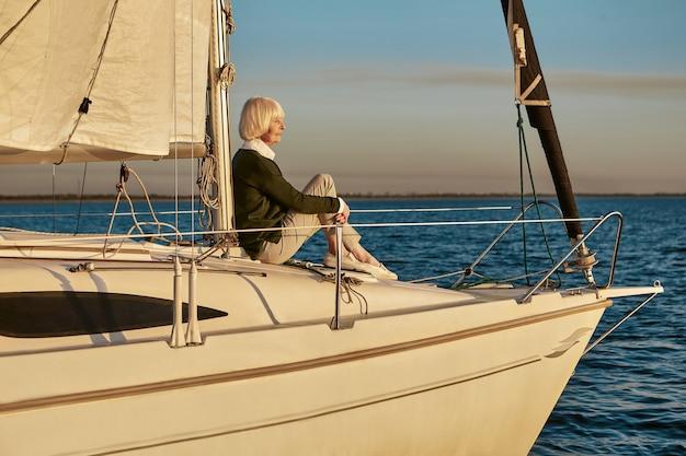 Старшая расслабленная женщина, сидящая на борту парусной лодки или палубы яхты, плавающей в спокойном синем море в