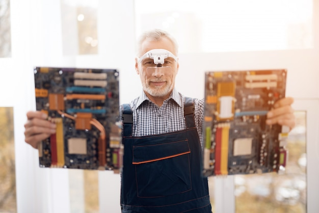 Senior repairman is holding two motherboards.
