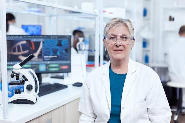 研究室の主任研究員が職場の職場に座ってカメラを見ています。白衣を着た年配の科学者が、アフリカの助手を背景に新しい医療用ワクチンの開発に取り組んでいます。