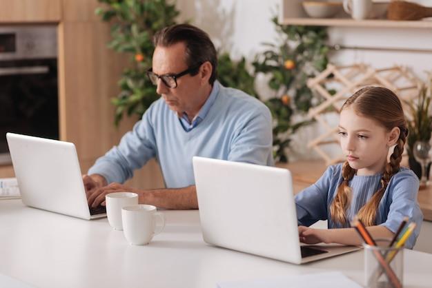 Старший пенсионер-нелюбопытный мужчина сидит дома и использует ноутбук с внучкой, играя в игры и проверяя профили в социальных сетях