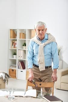 家庭環境で開いたノートブックと椅子とテーブルのそばに立っている間あなたを見ているカジュアルウェアのシニア引退した男