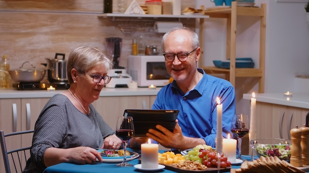 Senior retired old husband showing photos on tablet to his wife during romantic dinner. couple sitting at the table, browsing, talking, using internet, celebrating their anniversary in dining room.
