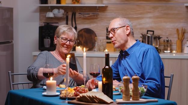 Старшая пожилая пенсионерка показывает фотографии на смартфоне мужу во время романтического ужина. пара сидит за столом, разговаривает, по телефону, отмечает годовщину в столовой.