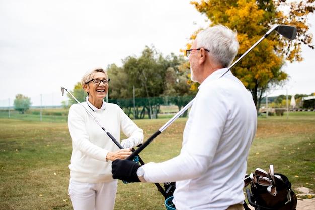 Пожилые пенсионеры, проводящие свободное время на природе, играя в гольф и развлекаясь на поле для гольфа