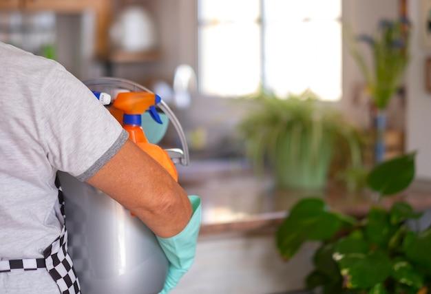 掃除用品がいっぱい入ったバケツを持って家の衛生作業で忙しい年配の引退した女性