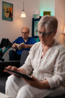 デジタルタブレットガジェットを見ている年配の引退した女性