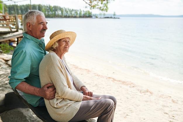 Старшие романтические мужчина и женщина сидят на пляже у озера, наслаждаясь отдыхом и погодой