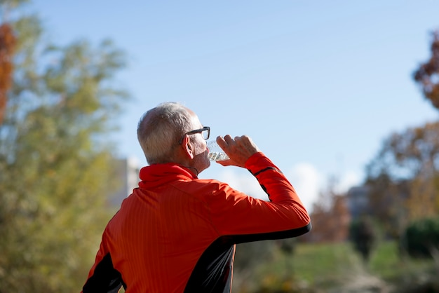 Senior runner drinking water after jogging