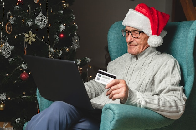 Senior in a santa claus hat sits in an armchair using laptop hoding credit card