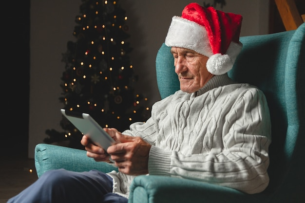 Senior in a santa claus hat sits in an armchair using tablet on the design of a christmas tree