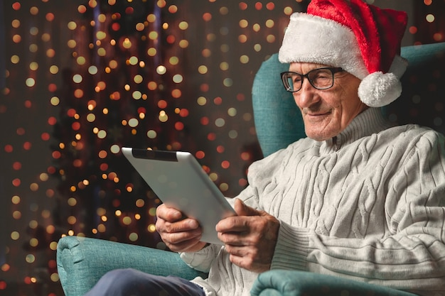 Senior in a santa claus hat sits in an armchair and using tablet