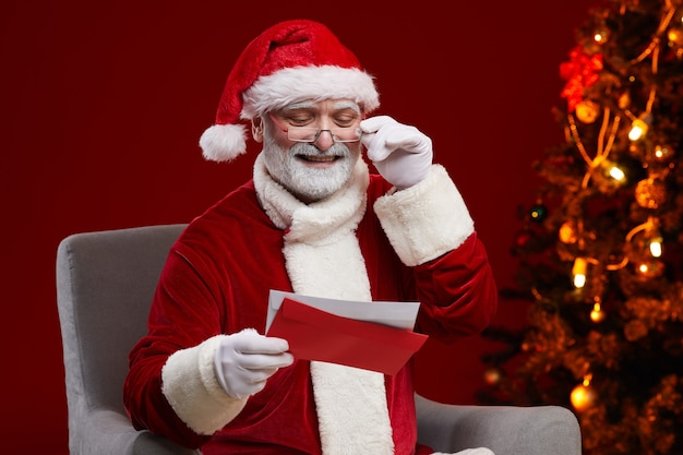 クリスマスツリーの近くの彼の肘掛け椅子に座っている子供たちからの手紙を受け取る赤い衣装を着たシニアサンタクロース