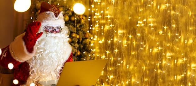 빨간 전통 의상을 입은 고위 산타가 크리스마스 파티를 통해 화상 통화를 하는 동안 노트북으로 온라인 채팅을 하고 있습니다.