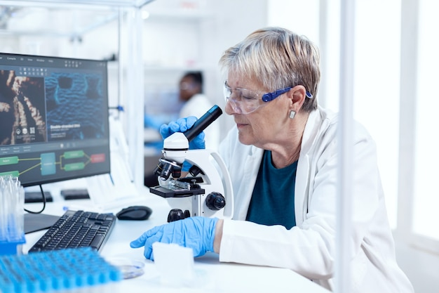 Старший научный сотрудник анализирует образец генетического материала с помощью микроскопа и африканский коллега на заднем плане. пожилой исследователь, проводящий научные исследования в стерильной лаборатории с использованием современных технологий.