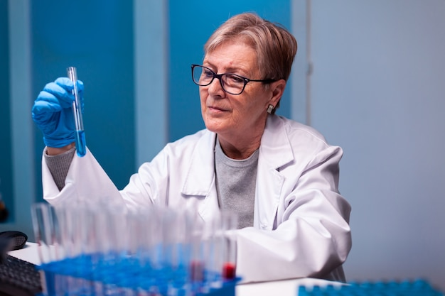 Senior scientist picking up sample with chemicals in test tube wearing gloves and protective glasses