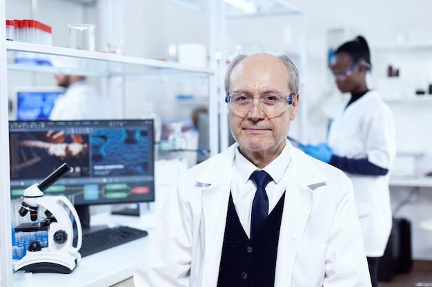 医療実験中に職場に座っている上級科学者。白衣を着た年配の科学者が、アフリカの助手を背景に新しい医療用ワクチンの開発に取り組んでいます。