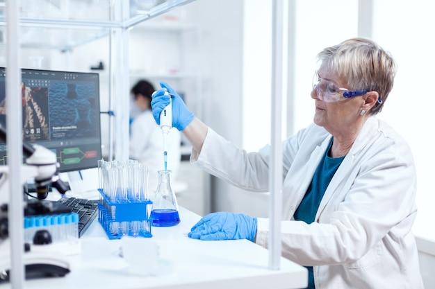 Старший научный сотрудник, принимая раствор из стеклянной колбы с помощью молекулярной пипетки. люди в инновационной фармацевтической лаборатории с современным медицинским оборудованием для генетических исследований.