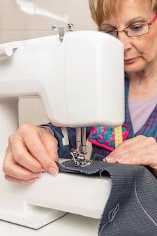 Старшая швея женщина работает с предметом одежды на швейной машине