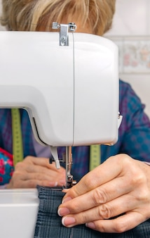 Senior seamstress woman working with clothing item on a sewing machine