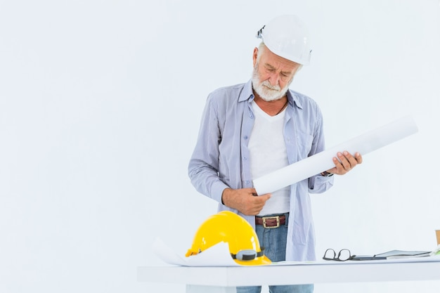 Senior serious construction engineer with hard hat hand holding blueprint in studio with white space for text