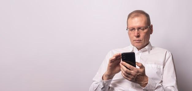 携帯電話、テキストメッセージ、またはインターネットサーフィンを保持している年配の真面目な男。テキストの場所と水平バナー