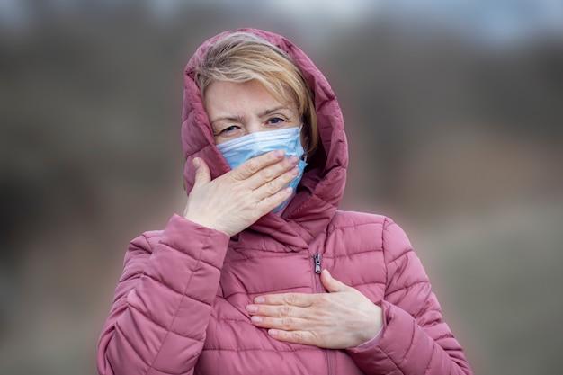 彼女の顔、咳、彼女の胸、肺に手を握って医療滅菌マスクでシニアの病気病気の深刻な女性。パンデミック、ウイルス、covid-19コンセプト。コロナウイルス症状