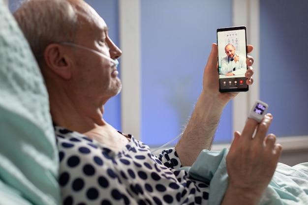 こんにちはと言って酸素チューブを通して呼吸する年配の病人