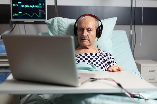 Senior sick man in hospital bed breathing through oxygen mask