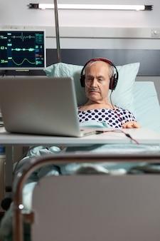 산소 마스크를 통해 호흡하는 병원 침대에서 수석 아픈 남자