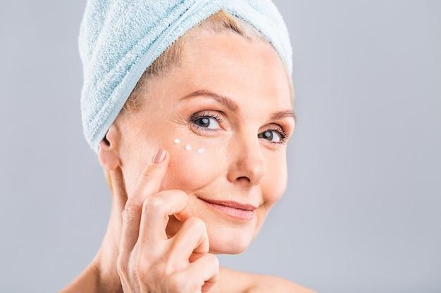 Старший улыбается 50-х годов зрелая женщина среднего возраста пожилая женщина, наносящая крем для лица на лицо, глядя в камеру, анти-возраст здоровая сухая уход за кожей концепция терапии красоты старая процедура по уходу за кожей