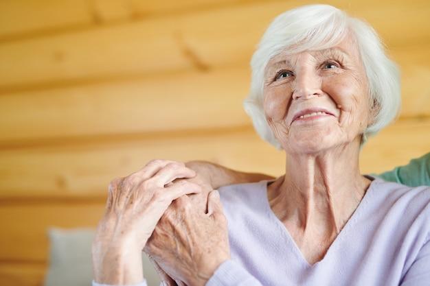 여가 시간에 그와 함께 tv 프로그램이나 영화를 보는 동안 그녀의 어깨에 남편 손을 만지고 수석 웃는 캐주얼 여자