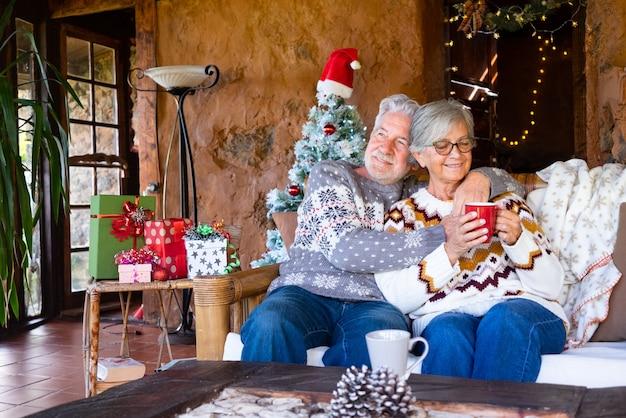 Старшие улыбающиеся пара, сидя у себя дома в деревенском шале во время рождества, расслабляясь на диване. рождественская елка, подарки и украшения на фоне