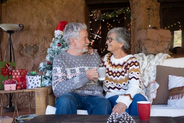 Старшие улыбающиеся пара, сидя на диване у себя дома во время рождества, расслабляясь и глядя друг на друга. рождественская елка, подарки и украшения на фоне