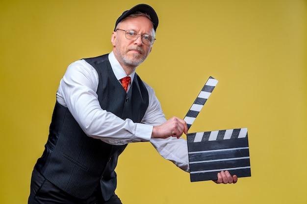 Старший улыбающийся режиссер с откидной крышкой. желтый фон. экранизация. режиссура фильма. производство фильма. человеческие эмоции.