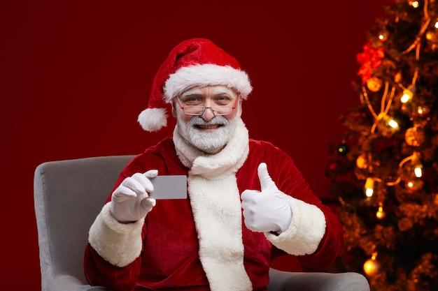 Старший улыбающийся человек в костюме санта-клауса держит визитную карточку и показывает палец вверх, сидя на кресле
