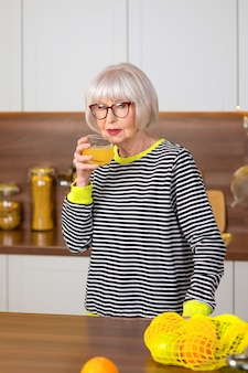 Senior smiling woman in striped sweater holding orange and drinking orange juice in the kitchen