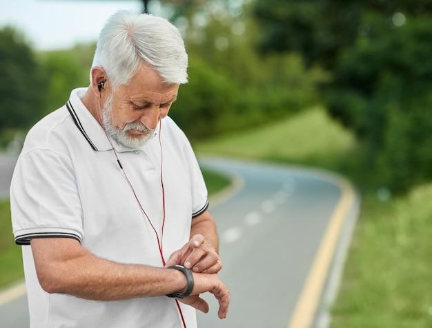 Старший спортсмен, глядя на часы во время утренней пробежки.