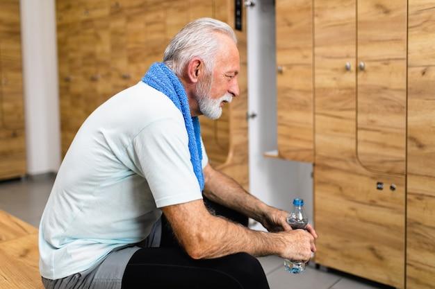 체육관의 라커룸에 물 한 병을 들고 서 있는 수석 스포츠맨.