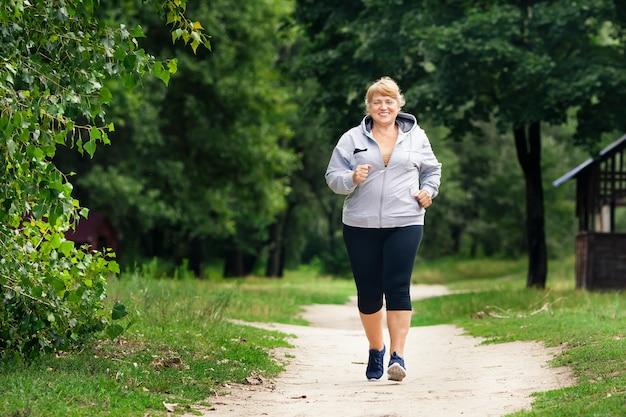 Старшая спортивная женщина бежит в летний парк
