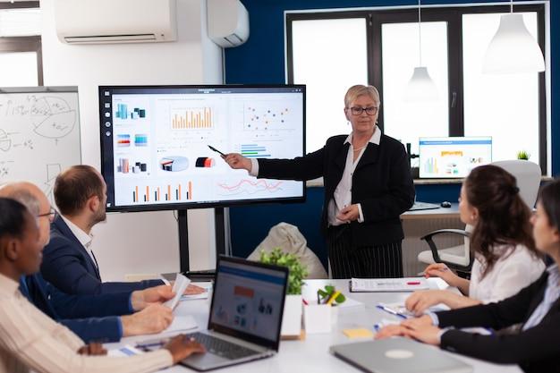 Старший стартап бизнесвумен держит презентацию в конференц-зале, информация о графике брифинга