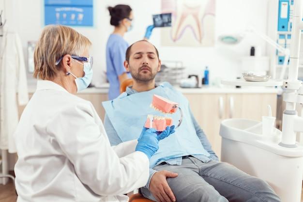 歯のモデルを使用して病気の患者の歯科治療を説明する上級歯科医