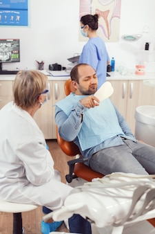 Senior stomatologist woman finishing dental surgery for man patient sitting on stomatology chair looking at tooth